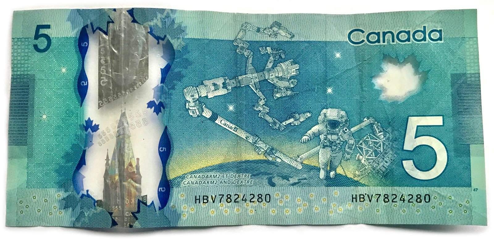 تصویر پشت اسکناس 5 دلاری کانادا، متعلق به ربات بازوی کانادایی به نام Canadarm میباشد
